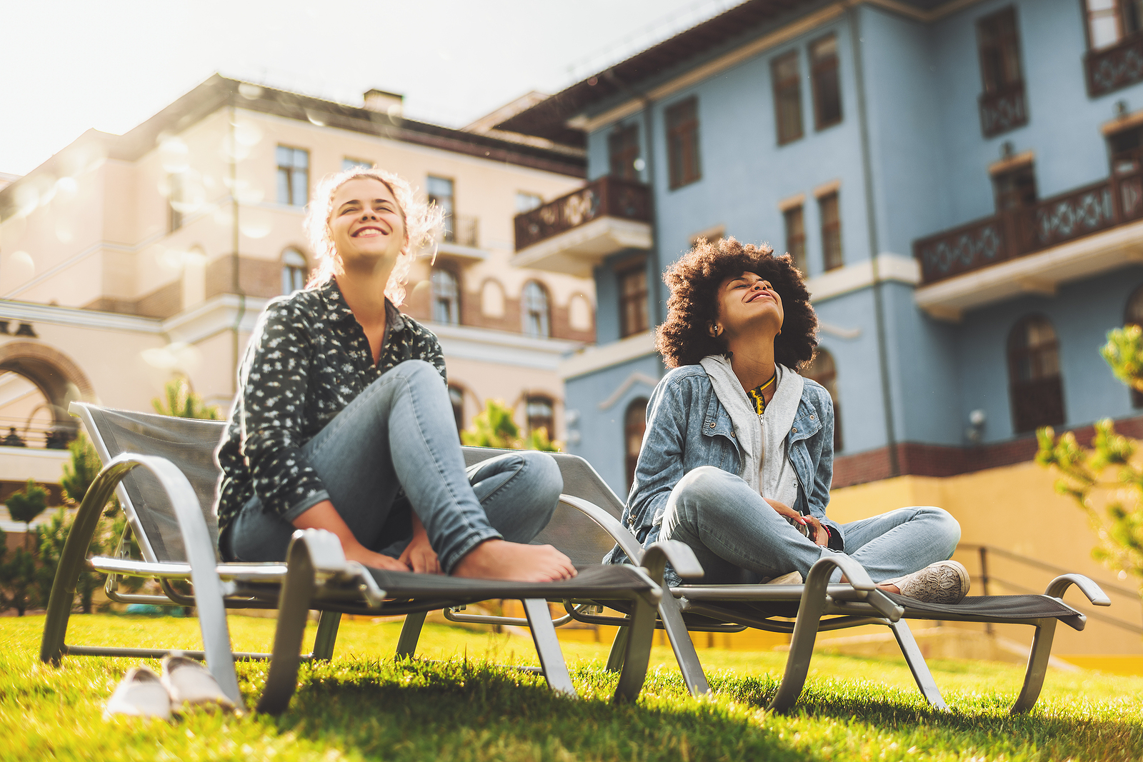 Black and Caucasian female friends on daybeds are sitting outdoors on the lawn and enjoying bright spring sun; two squinting girls of different races sitting on the recliners outdoor on the grass