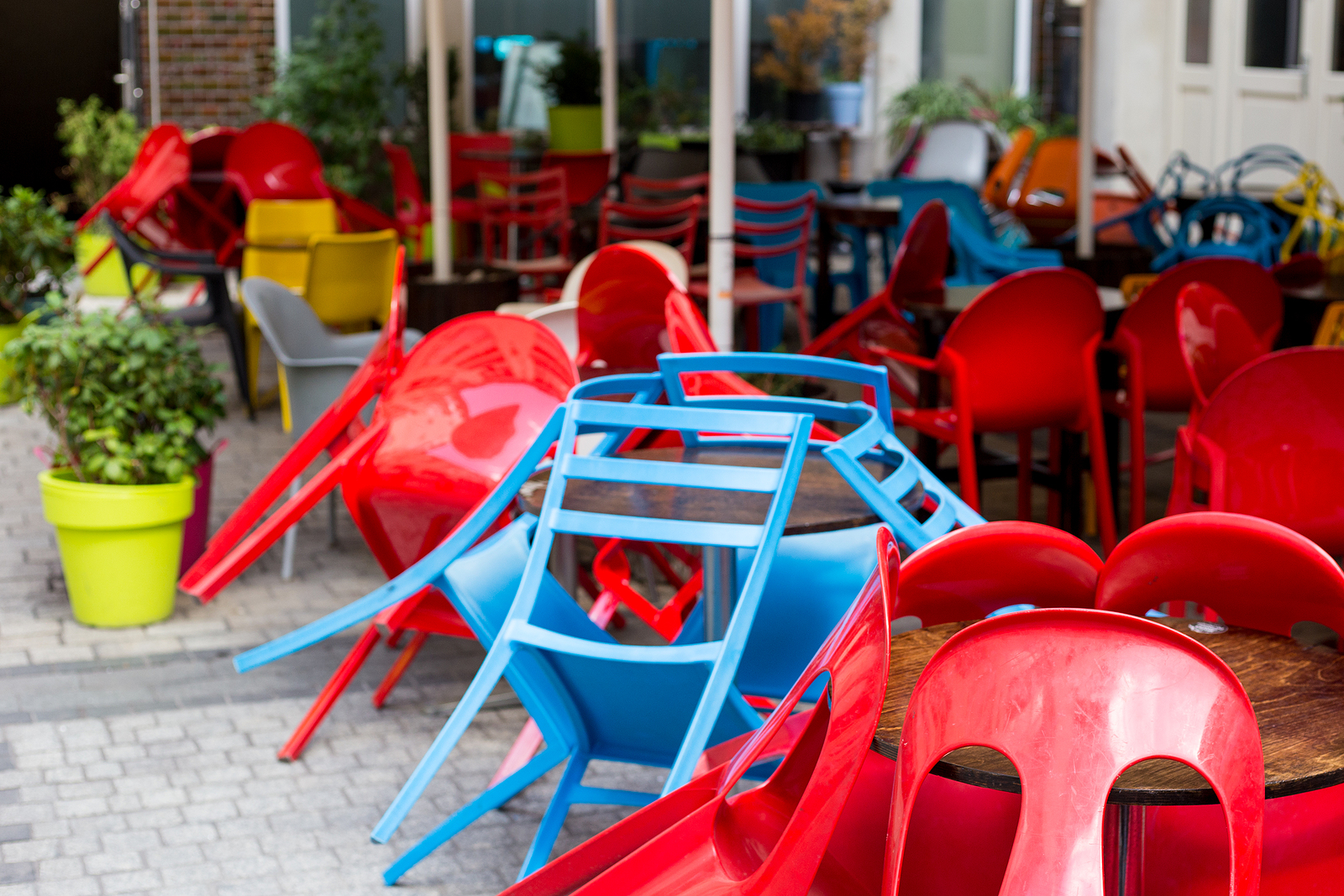 Colourful tables and chairs in a cafe. Yellow, blue, red colors. Outdoor