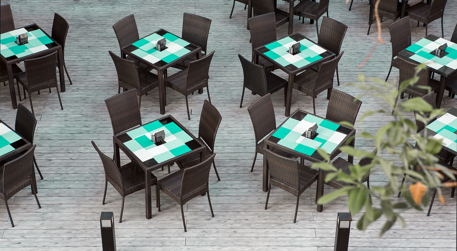 Dining tables and chairs on decking in outdoor restaurant area
